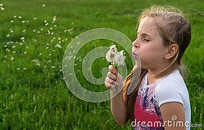 Pretty girl blowing dandelion