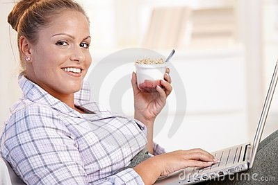 Pretty girl browsing Internet in bed smiling