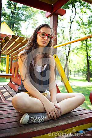 Pretty girl on climbing frame in park