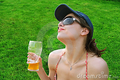 The pretty girl is drinking beer on the grass
