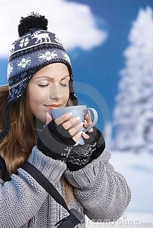 Pretty girl drinking hot tea in winter eyes closed