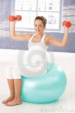 Pretty girl exercising with dumbbells on fitball
