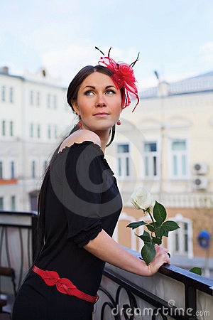 Pretty girl with flower on balcony outdoor