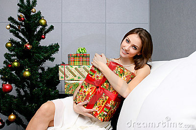 Pretty girl with gift near the Christmas tree