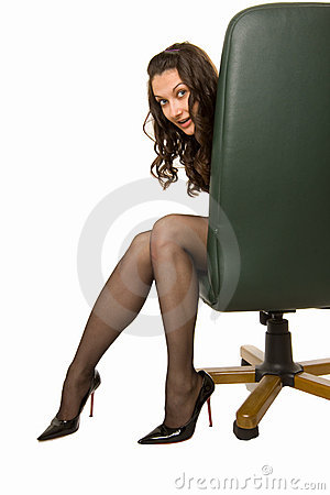Pretty girl hiding behind a chair but looking out