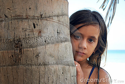 Pretty girl hiding behind a tree