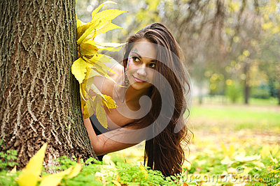 Pretty girl hiding behind a tree