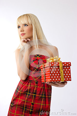 Pretty girl holding christmas gift in red dress