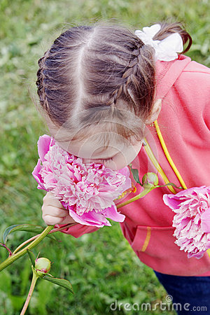 Pretty girl inhales the scent of a big pink flower