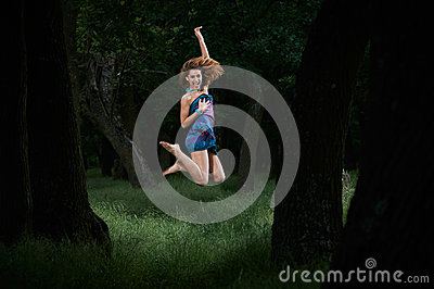Pretty girl jumping in woods