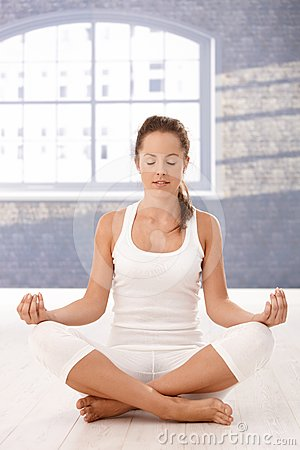 Pretty girl meditating in yoga studio eyes closed