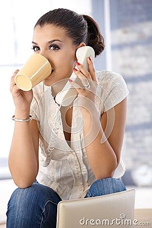 Pretty girl on phone drinking tea