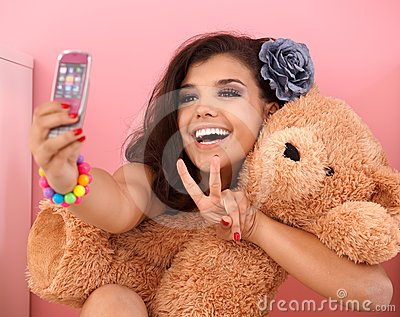 Pretty girl photographing herself and toy bear