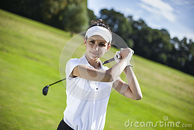Pretty girl playing golf on grass