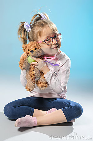 Free Pretty Girl Plays In The Doctor Treats A Teddy Bear On A Gray Ba Stock Images - 84730094
