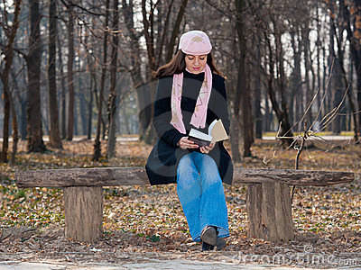 Pretty girl reading a book outdoor