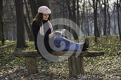 Pretty girl reading outdoors