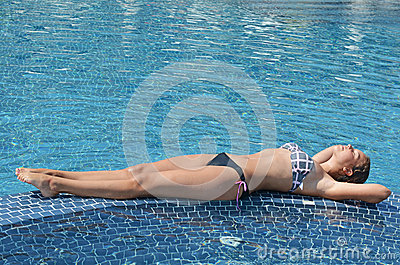 Pretty girl relaxing in the swimming pool