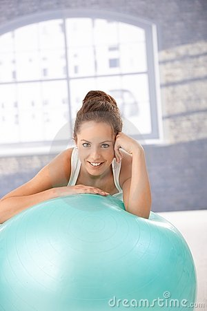 Pretty girl resting on fitball after workout