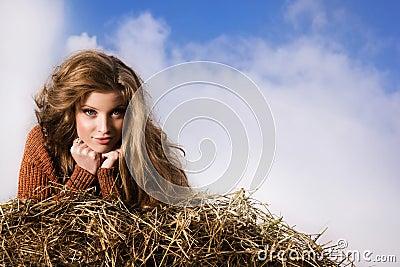 Pretty girl resting on straw bale