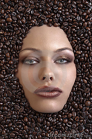 Pretty girl s face immersed in coffee beans