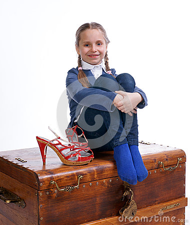 Pretty girl sitting on a box with moms shoes
