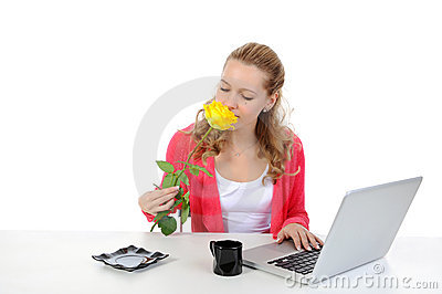 Pretty girl sniffing yellow rose.