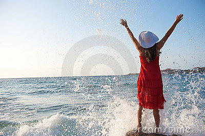 Pretty girl splashing by ocean wave