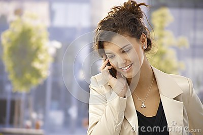 Pretty girl talking on mobile outdoors