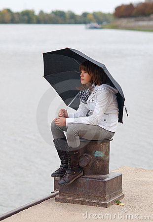 Pretty girl with umbrella sitting on the dock