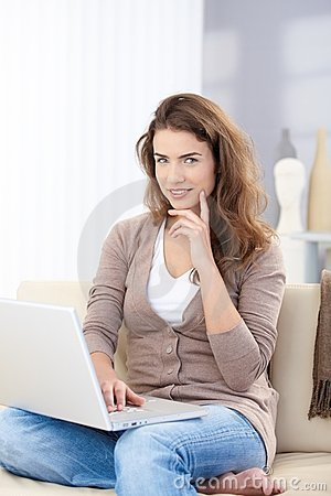 Pretty girl using laptop at home working