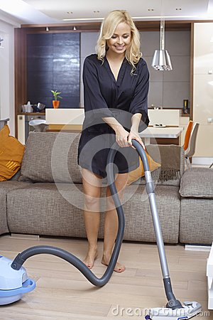 Pretty girl using vacuum cleaner at home