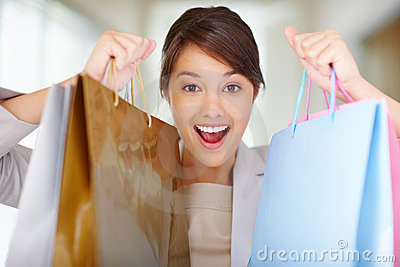 Pretty happy female holding  shopping bags