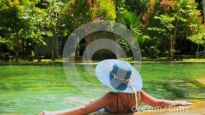 Pretty lady in a blue swimsuit, hat and sunglasses sits and relaxes legs down in the water near tropical swimming pool stock video footage