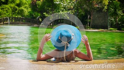 Pretty lady in a blue swimsuit, hat and sunglasses sits and relaxes in tropical swimming pool with clear water on a stock footage