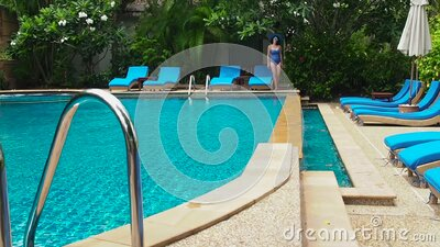 Pretty lady in a blue swimsuit, hat and sunglasses walking around swimming pool with clear water on a sunny day stock footage