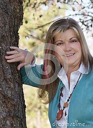 Pretty lady posing near a tree