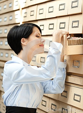 Pretty lady seeks something in card catalog