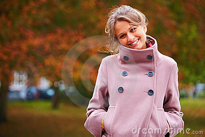 Pretty lady smiling with hands in pockets