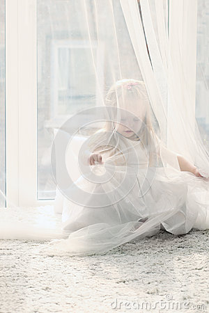 Free Pretty Little Blonde Girl Sits Near Big Window And Hides Royalty Free Stock Image - 42649766