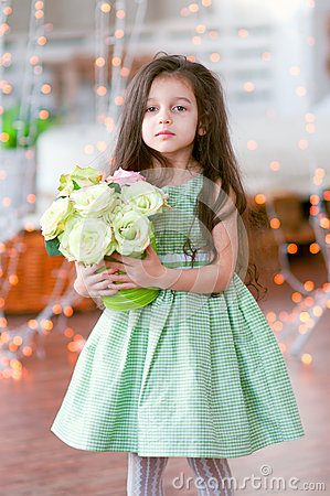 Pretty little girl in beautiful green dress with r