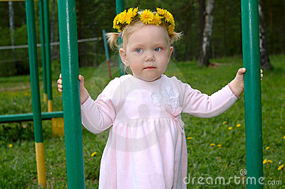 Pretty little girl with dandelion flower garland.