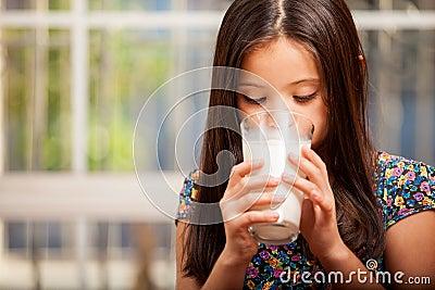 Pretty little girl drinking milk