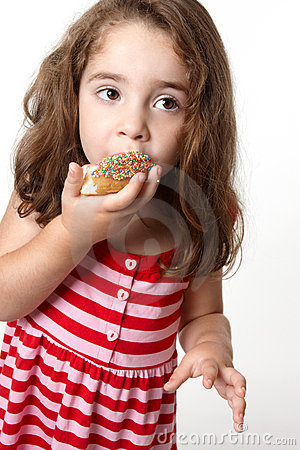 Pretty little girl eating a doughnut