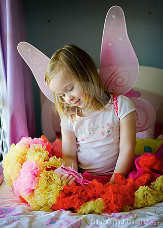 A pretty little girl on her bed in a fairy costume