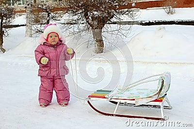 Pretty little girl near sled (sleigh).