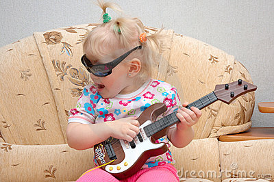 Pretty little girl play on toy guitar.