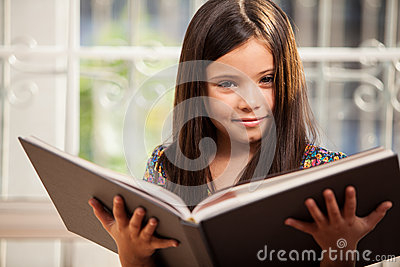 Pretty little girl reading a story