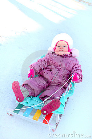 Pretty little girl sit on sled (sleigh).