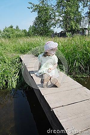 Free Pretty Little Girl Sits On Small Bridge In Village Stock Photo - 37073540